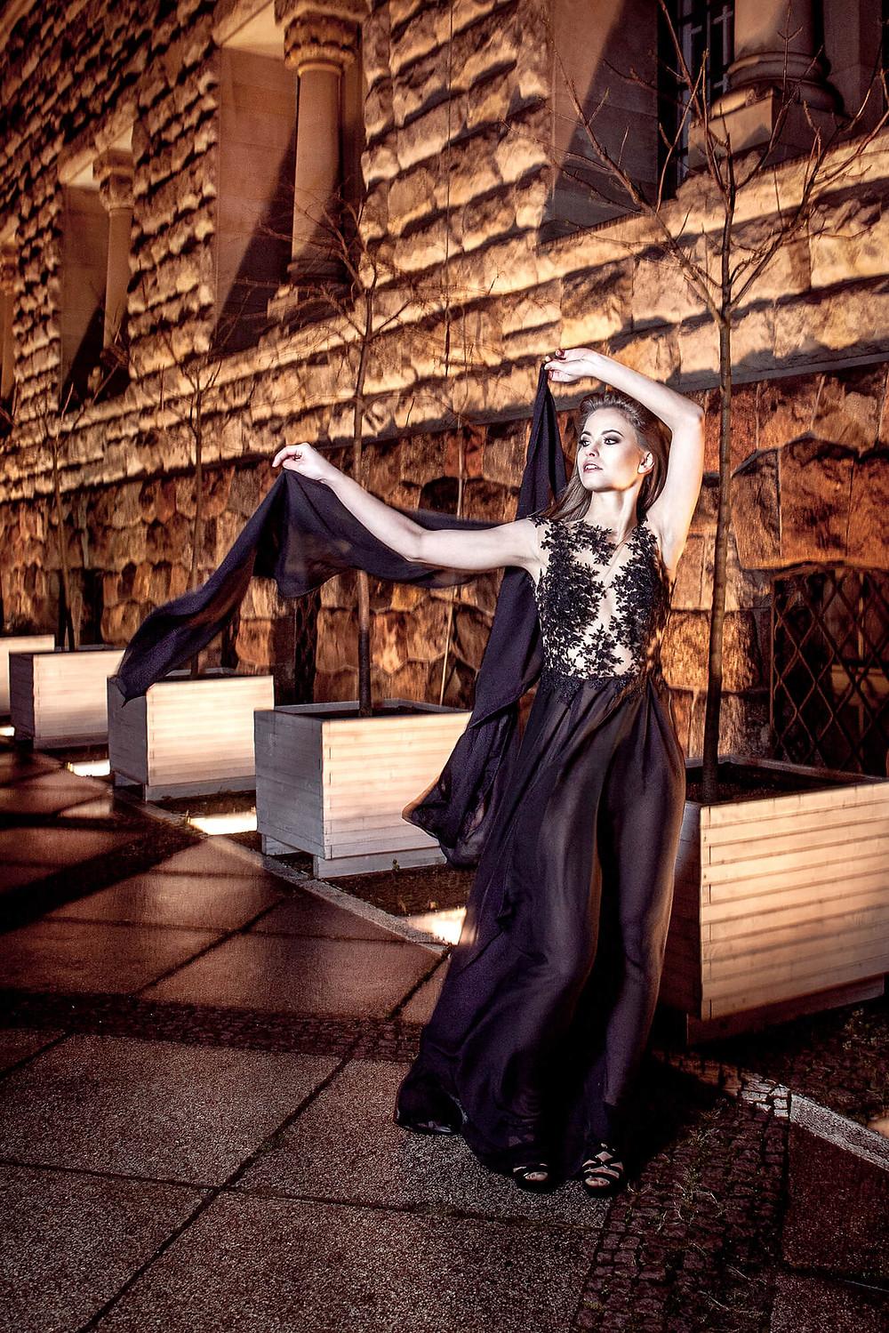 Edytorial fashion, modelka biegnie w długiej, czarnej sukni