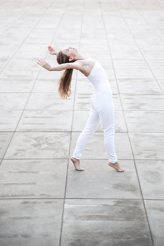 Ubrana na biało tancerka wygina się do tyłu