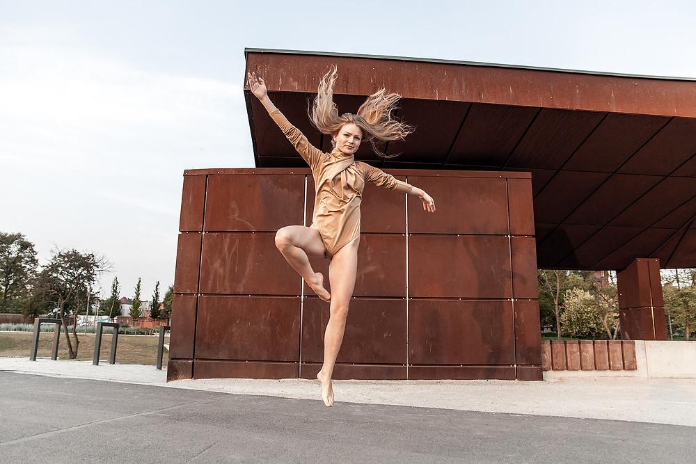 Dynamiczne zdjęcie tancerki w skoku na tle budowli z blachy