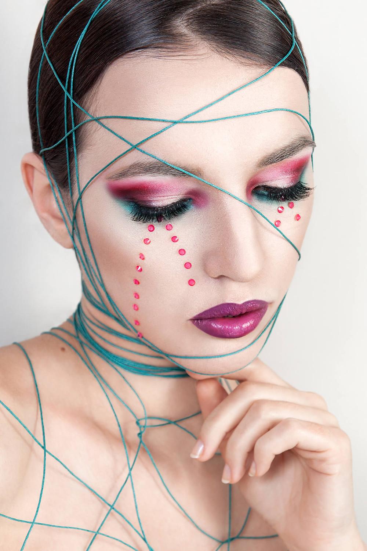 Modelka w pięknym, różowo fioletowym makijażu z turkusowym akcentem