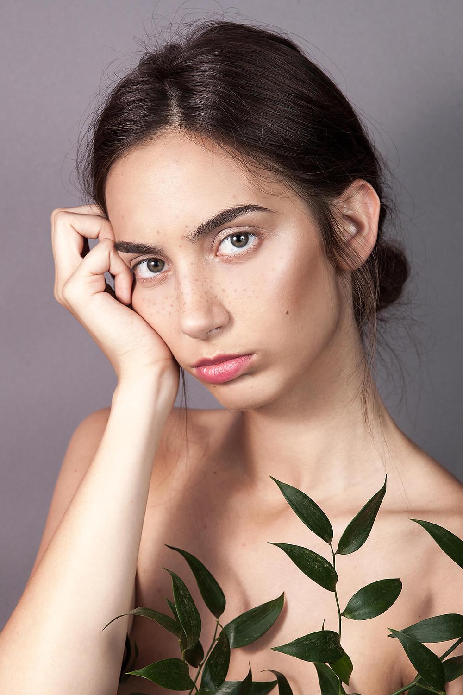 Zamyślona modelka w delikatnym makijażu na szarym tle