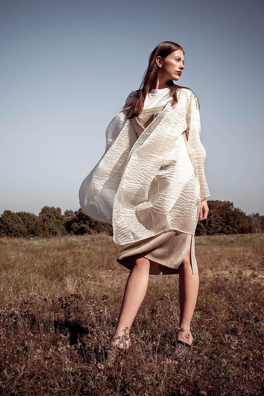Edytorial high fashion, lśniąca stylizacja na tle rozległej przestrzeni