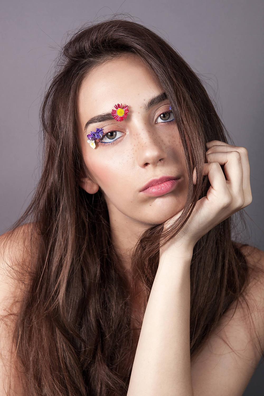 Zamyślona modelka z płatkami kwiatów przyklejonymi do twarzy