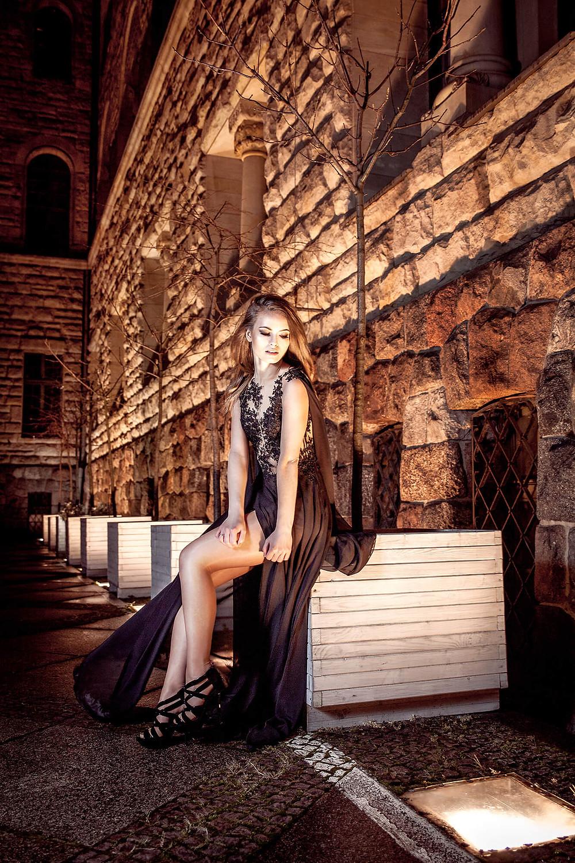 Modelka w pięknej, wieczorowej sukni siedzi na tle zabytkowej architektury