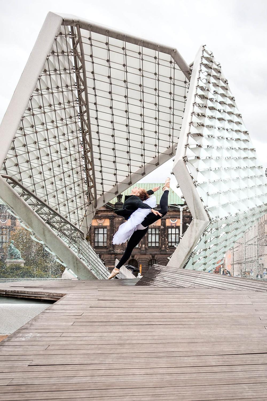 Baletnica w skoku na tle fontanny na Placu Wolności