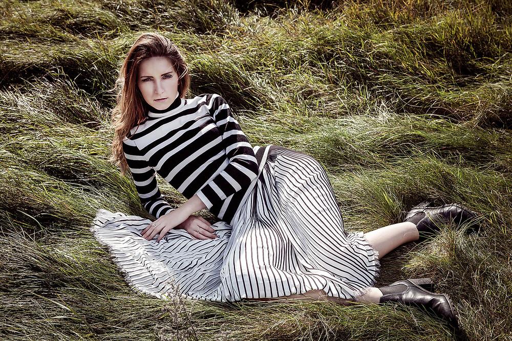 Modelka w stylizacji w biało-czarne pasy leży w wysokiej trawie