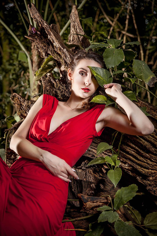 Modelka w czerwonej sukni siedzi w otoczeniu egzotycznych roślin