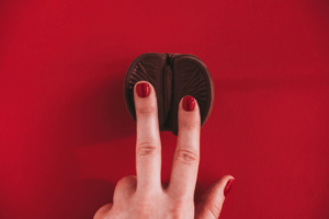 Two fingers on a chocolate clitoris