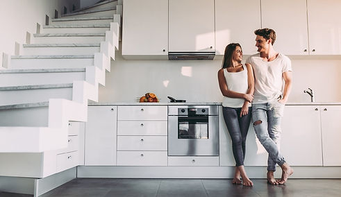young couple smiling in clean house