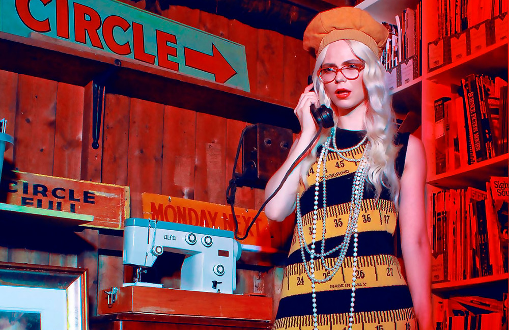 Woman in an independent cinema booking office, wearing red glasses, answering a retro telephone and looking extremely surprised