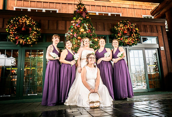 Bride and Bridesmades posing in front of the Heathman Lodge at Christmas time.