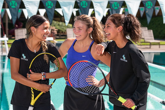 three girls laughing holding tennis rackets