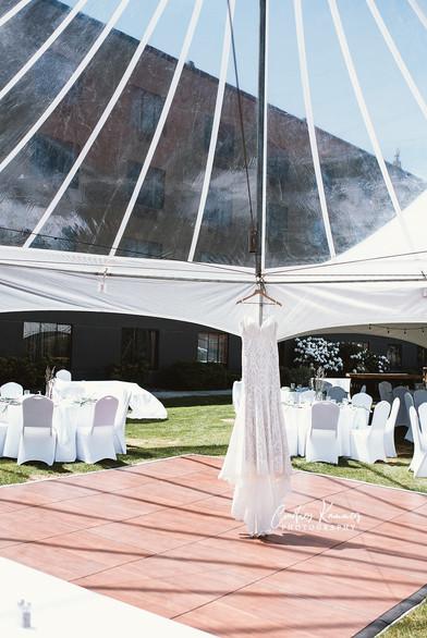 Wedding dress hanging in outdoor event tent