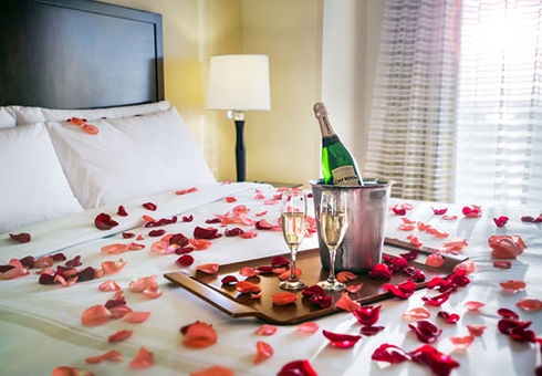 Champagne and roses on the bed