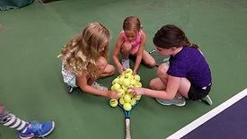 kids stacking up tennis balls on a racket