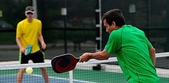 Man hitting ball playing pickleball