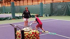 child and coach teaching tennis