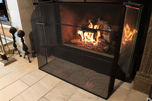 Custom curved mesh firescreen with matte black handles and finish