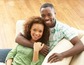 Black couple sitting on sofa