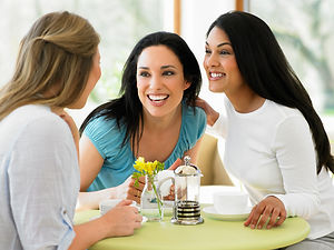Three young women chatting at a table.