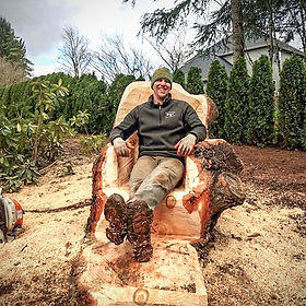 Natha Herford carving a tree throne from a tree stump