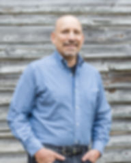 Ron Rosenberg in front of a barn, offers speaking and training programs.