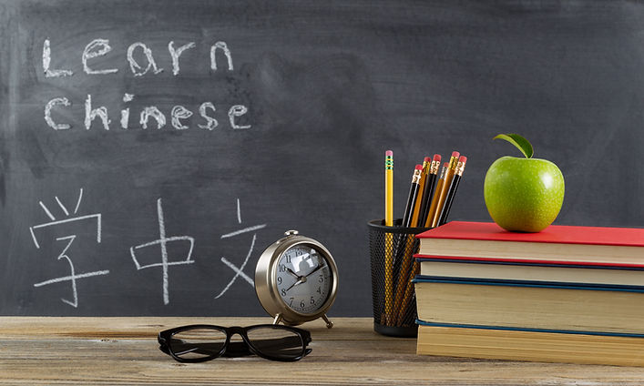 Student learning Chinese with books, pen