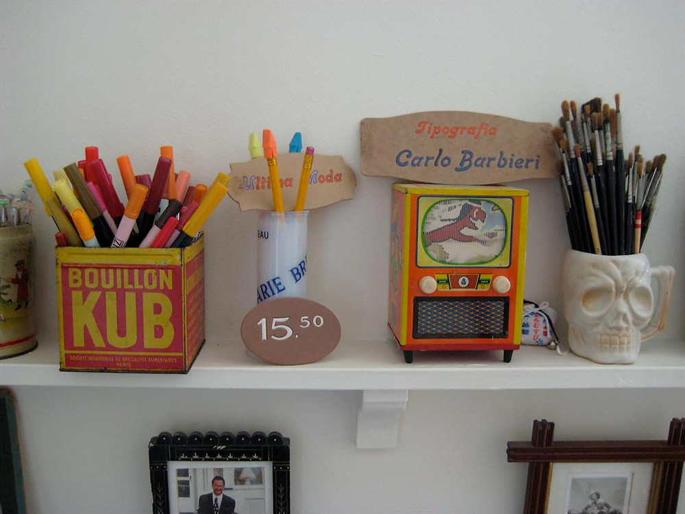 paintbrushes  and markers on a shelf