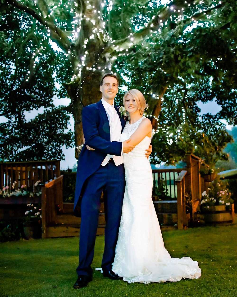 Wedding couple pose for photos under tree