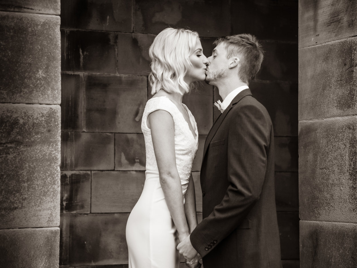 Bride is photographed kissing the groom