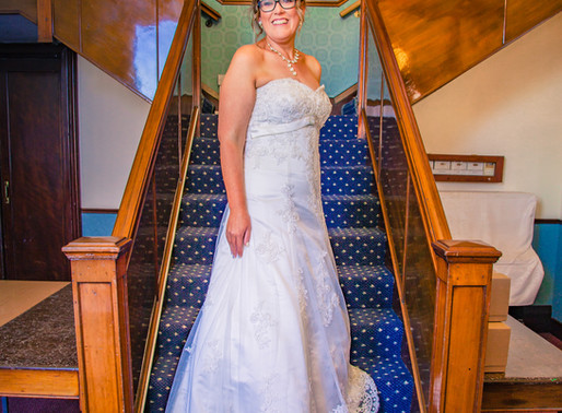 Bride poses for photographs on the stairs at Stockton Masonic Hall