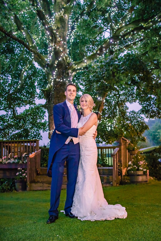Bride & groom pose under a tree
