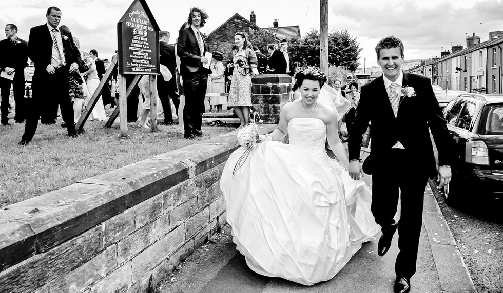 Wedding couple leave the church ceremony