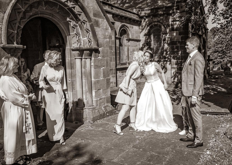 Candid wedding photograph of bride & groom receive wedding guests