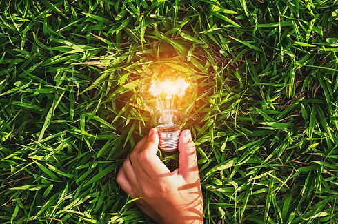 hand hold light bulb on grass  with suns