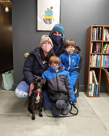 A family posing with their dog adopted via Waggytail Rescue