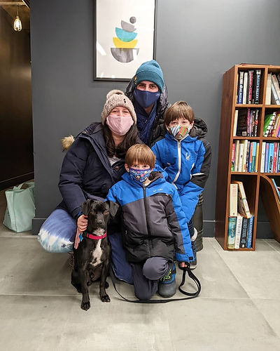 A family (father, mother, and two sons) with their newly adopted dog from Waggytail Rescue