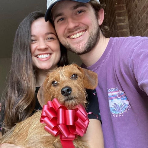 A couple holding up their dog adopted via Waggytail Rescue