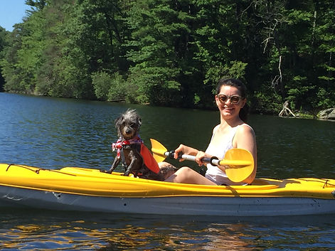 A picture of a woman and her newly adopted dog on a kayak after adopting from waggytail rescue