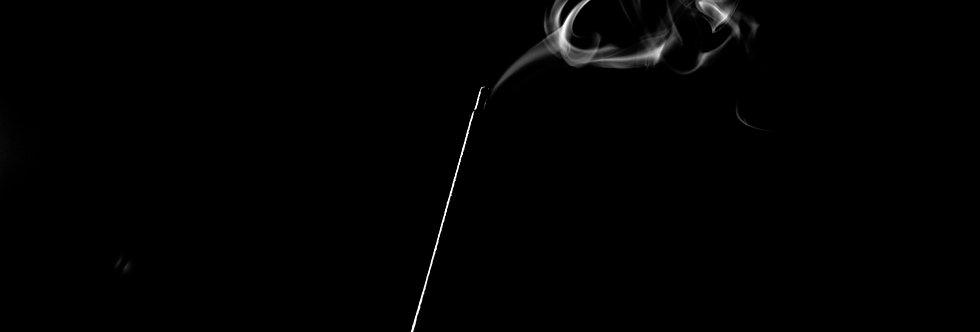 Bastoncino d'incenso, luce radente, su nero