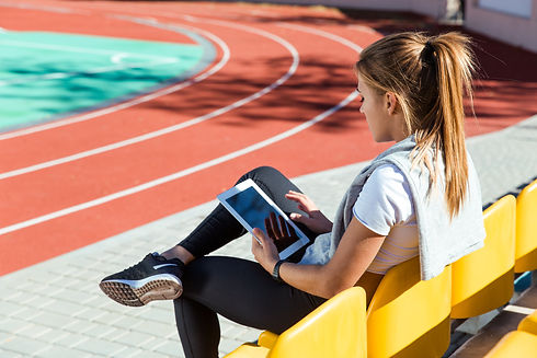 portrait-fitness-woman-resting-with-tablet-computer-outdoor-stadium.jpg