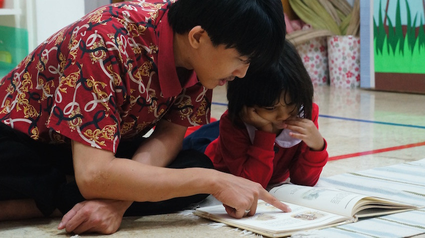 Child and teacher read a book together.