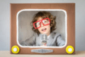Child playing with cardboard box TV. Kid