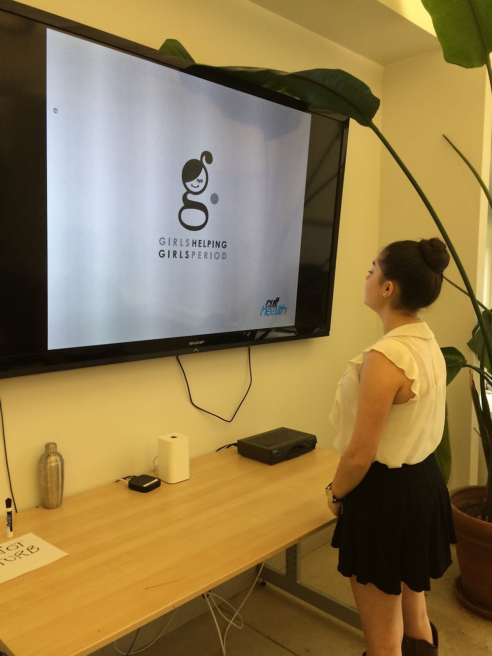 Emma looks at a screen with the new logo for Girls Helping Girls. Period.