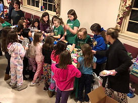 Girl Scouts pack period products they collected at a camping event