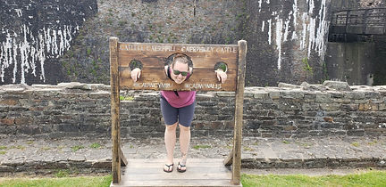 Standing in a pillory at Caerphilly Castle, in Caerphilly Wales