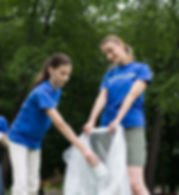 Two girls puting litter into a bag