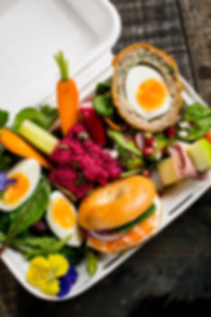 A composite picture showing various salad ingredients, a scotch egg and a salmon bagel.