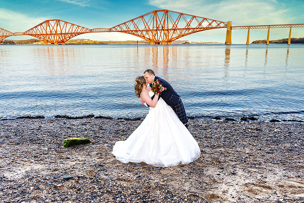 Bride & Groom Kiss on the beach with Forth Rail Bridge in Background, South Queensferry