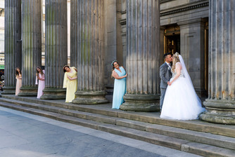 Bride & Groom Kiss at The GOMA in Glasgow. The Bridesmaids Sneak a Peek
